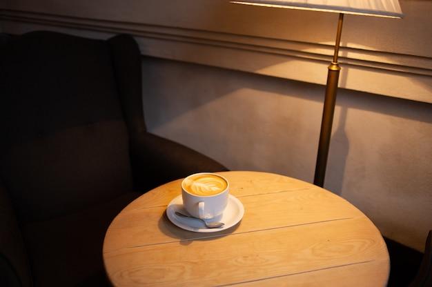 木製のテーブルの上のコーヒーカップとコーヒー豆。カフェの白いカップのラテ