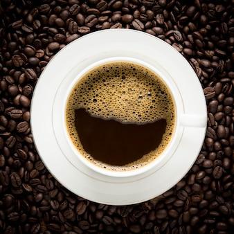 木製のテーブルの上のコーヒーカップとコーヒー豆