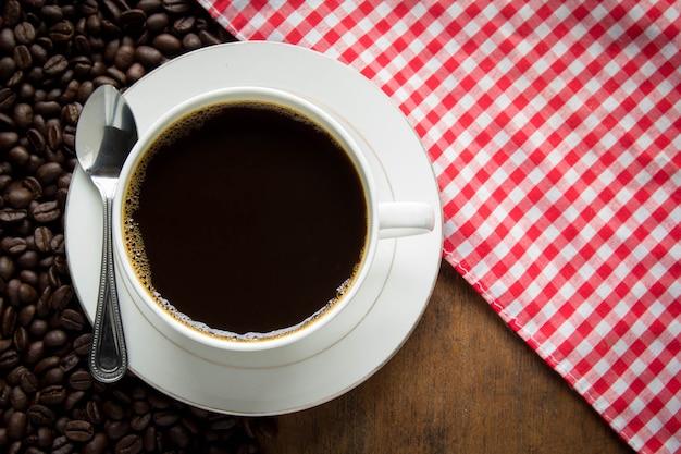 Чашка кофе и кофейные зерна на деревянном столе