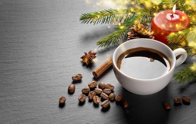 クリスマスの装飾モミの枝と暗い石のテクスチャテーブルに赤いろうそくを燃やすコーヒーカップとコーヒー豆。