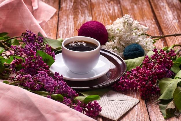 Чашка кофе и красочные сиреневые цветы на деревянном столе в саду