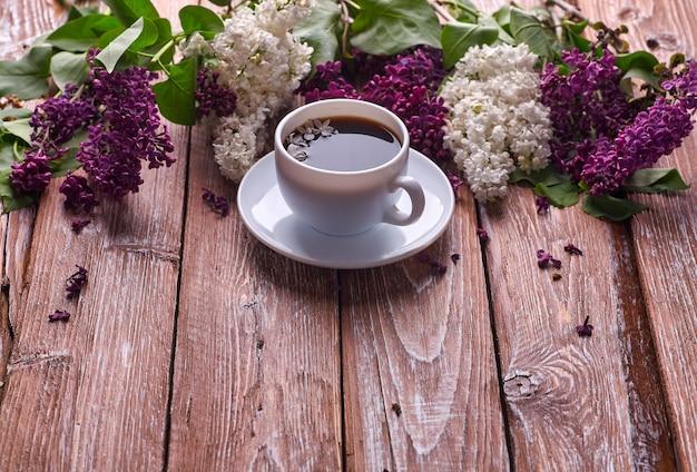 庭の木製テーブルの上のコーヒーカップとカラフルなライラックの花