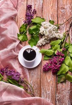 庭の木製テーブルにコーヒーカップと色とりどりのライラックの花。