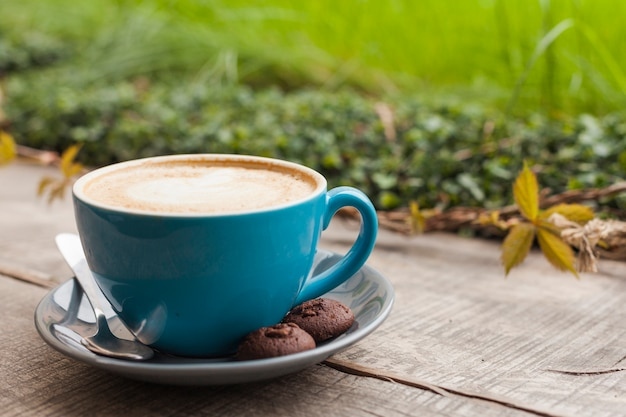 コーヒーカップとデフォーカス緑の自然の背景を持つ木製の表面上のクッキー