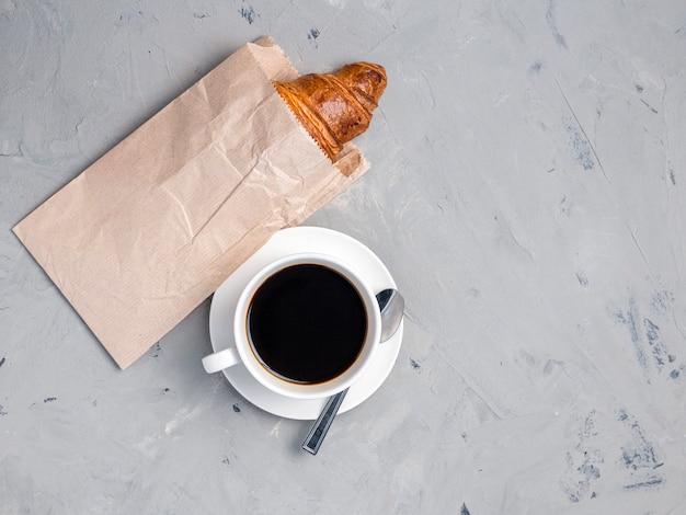 Чашка кофе и круассан в бумажной упаковке. идеальный завтрак по утрам. деревенский стиль, вид сверху