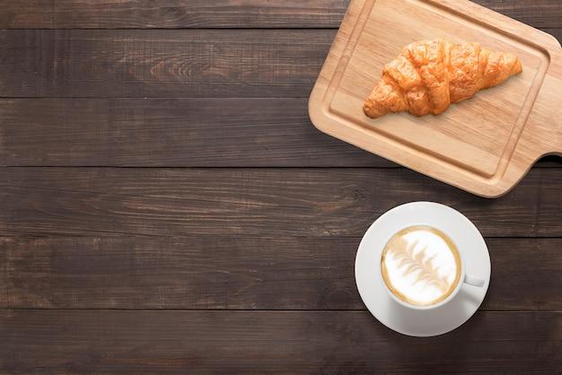 Кофейная чашка и свежие испеченные круассаны на деревянной предпосылке. вид сверху