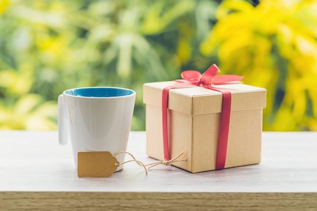 햇빛 나무 테이블에 커피 컵과 선물 상자.