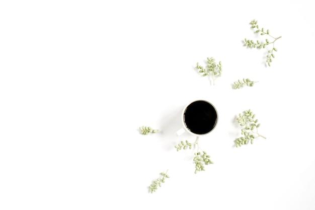白い表面にコーヒーカップと緑の枝
