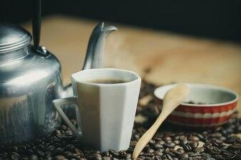 コーヒーカップとホットポットローストコーヒー豆。