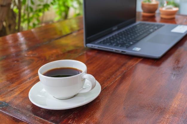 Чашка кофе и ноутбук на деревянном столе в саду