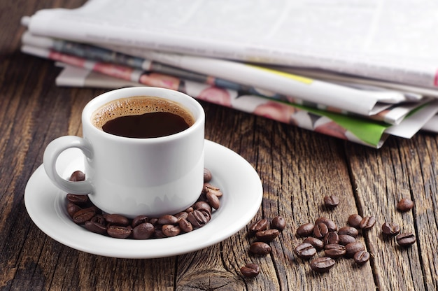 コーヒーカップと古い木製のテーブルの上の新聞