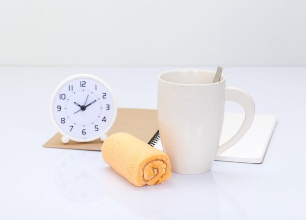 コーヒーカップとオフィスアクセサリーの背景とオレンジ色のロールケーキ