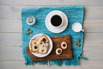 Coffee cup and pie with jam on table