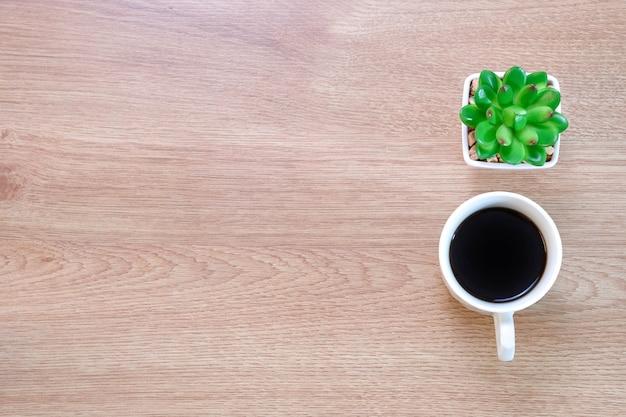 Чашка кофе и пластиковый кактус на фоне деревянного стола в кафе.