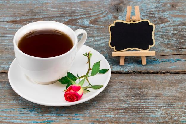 木製の上のテキストの空スペースで黒板にコーヒーカップと赤いバラ