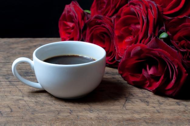 Кофейная чашка и красные розы позади этого.