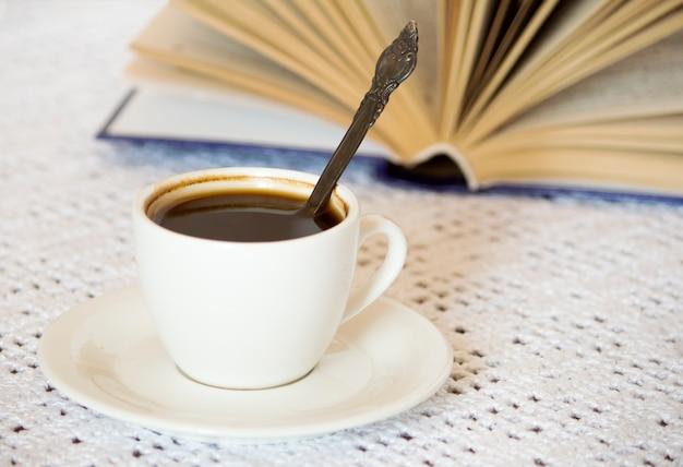 흰색 테이블 표면에 열린 책이 있는 커피 컵과 접시.
