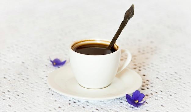 흰색 테이블 표면에 보라색 아프리카 보라색 꽃이 있는 커피 컵과 접시.