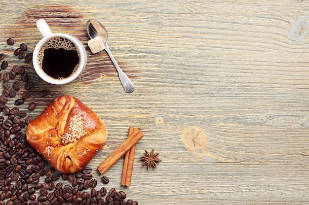 コーヒーカップと古い木製のテーブルに甘いパン