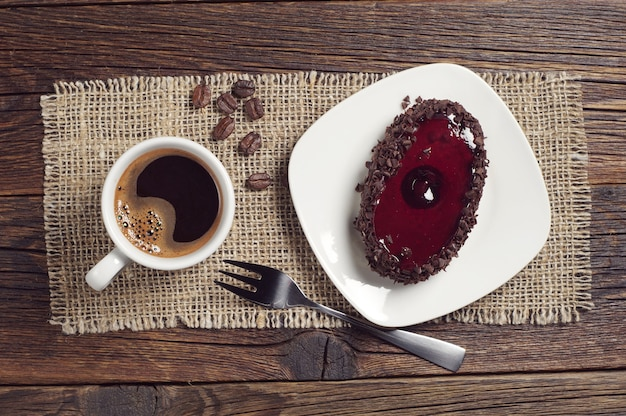 어두운 나무 테이블에 체리 젤리를 넣은 커피 컵과 맛있는 초콜릿 케이크, 위쪽 전망