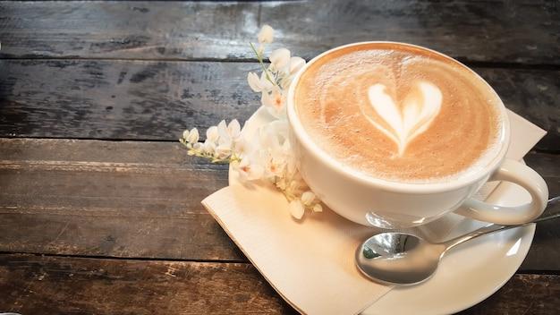 커피 컵과 나무 테이블에 작은 흰 꽃.