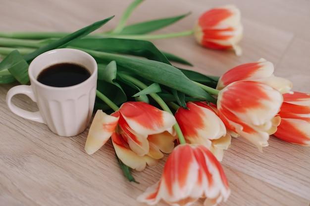 Чашка кофе и тюльпаны. концепция праздника, дня рождения, пасхи, 8 марта, дня святого валентина