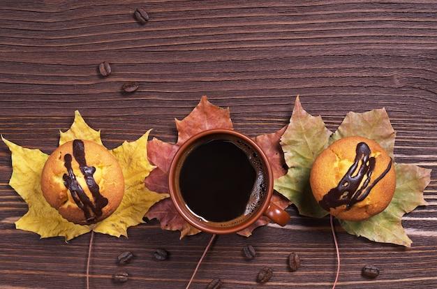 コーヒーカップと木製のテーブルにチョコレートと2つのカップケーキ