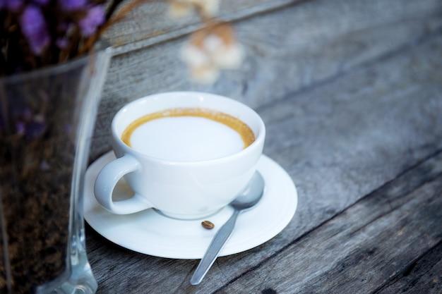 木製のテーブルの上のコーヒーカップと花瓶