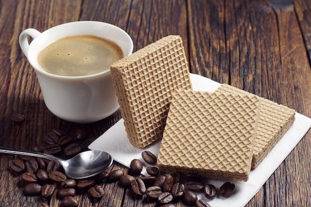 어두운 나무 테이블에 캐러멜 연유를 넣은 커피 컵과 웨이퍼