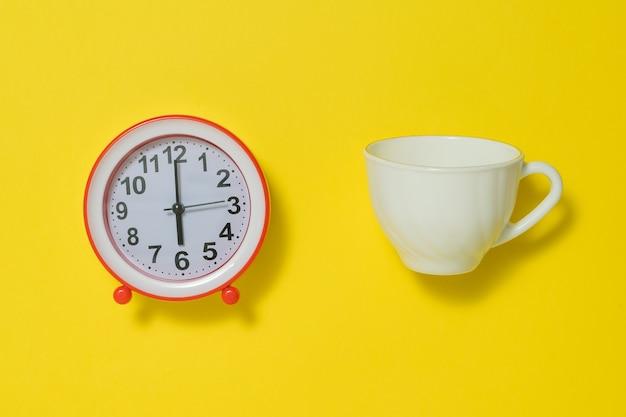 노란색 배경에 커피 컵과 흰색 아날로그 알람 시계. 아침에 톤을 들어 올리는 개념. 플랫 레이.