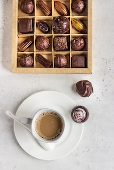 Coffee cup and assortment of fine chocolate candies on grey stone background.