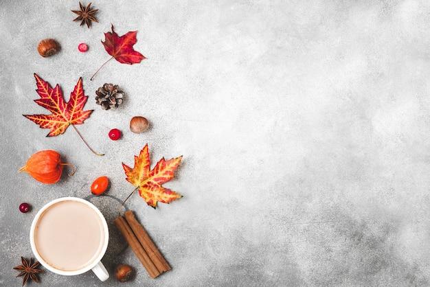 Чашка кофе, осенние листья, цветы, ягоды и орехи