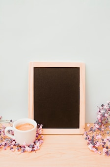 Coffee cup and baby's-breath flowers near the blank wooden slate against white wall