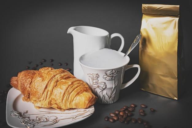 灰色の背景にisoaltedコーヒーカップ、バッグ、クロワッサン