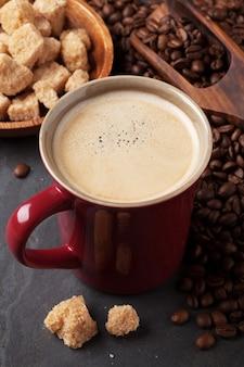 石のテーブルにコーヒーカップ、豆、黒糖
