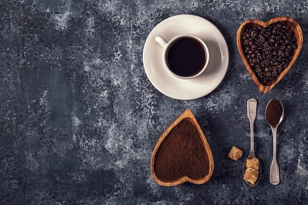石の背景にコーヒーカップ、豆、粉砕粉