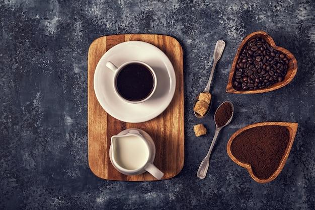 Чашка кофе, зерна и молотый порошок на каменной поверхности