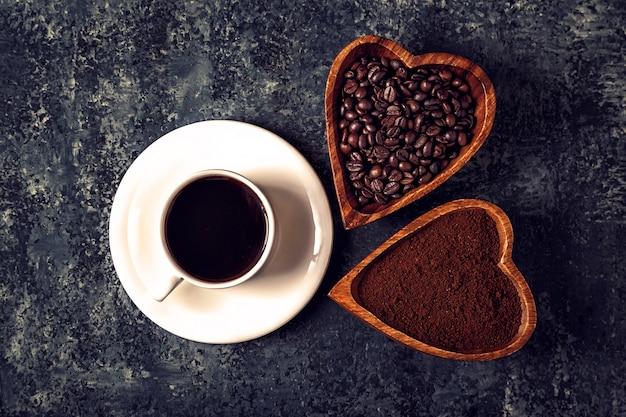 Кофейная чашка, фасоль и молотый порошок на каменном столе.