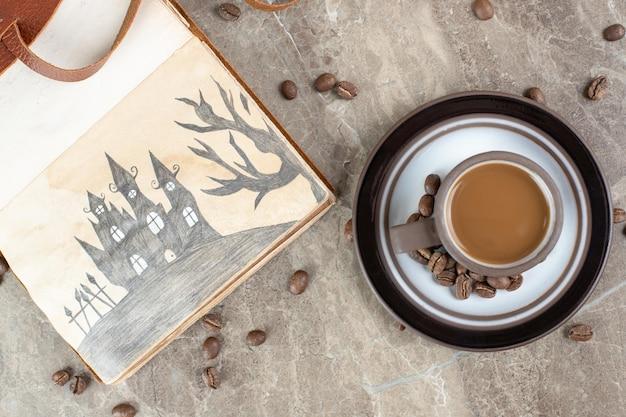 大理石の表面にコーヒーカップ、豆、ノートブック