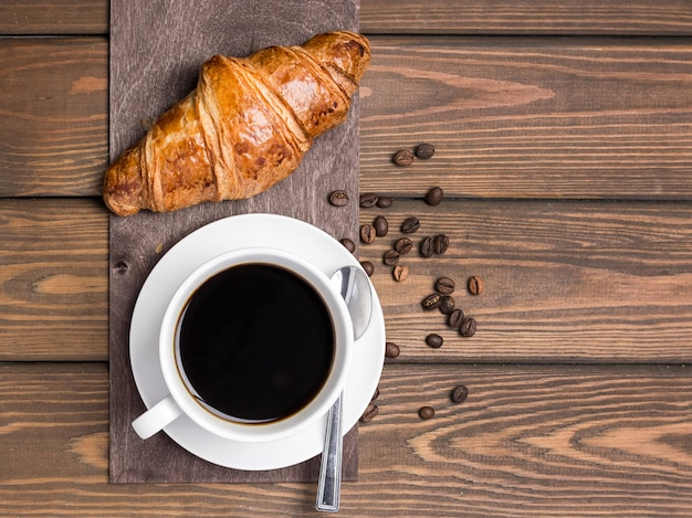 Coffee cup, beans and croissant on wooden background on the table