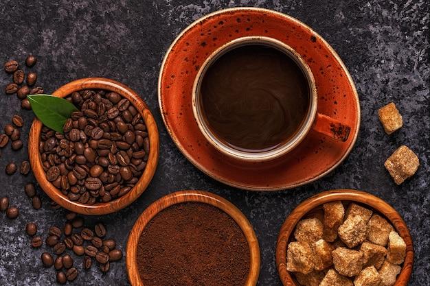 Чашка кофе, бобы, молотый порошок и сахар на каменном фоне