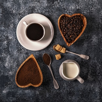 Coffee cup, beans and ground powder on stone background