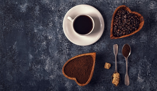 Coffee cup, beans and ground powder on stone table.