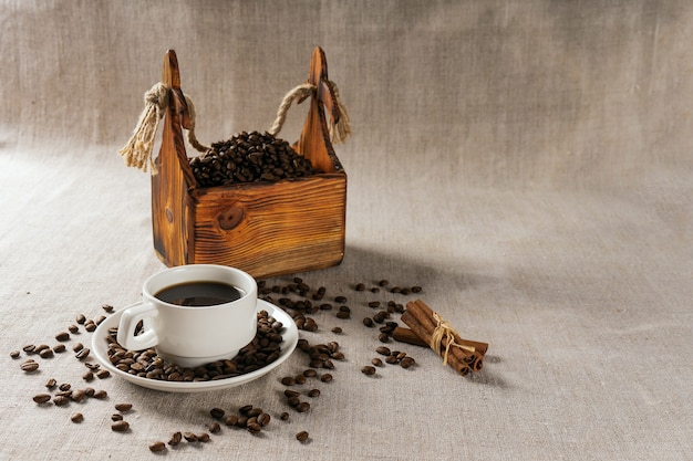 Coffee cup and beans on old kitchen table.