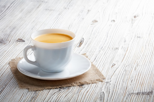 Coffee cup and beans on a white wood background.
