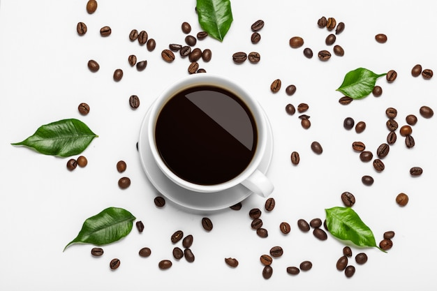 Coffee cup and beans on white