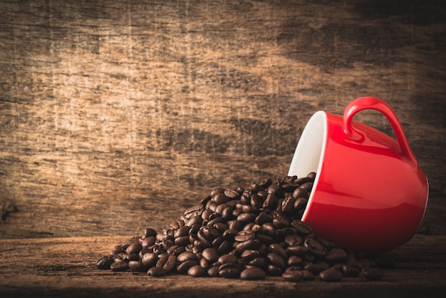 Coffee cup and beans on wood background