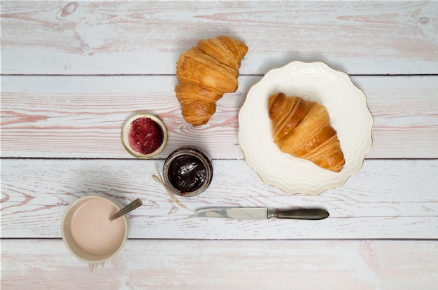 Coffee cup; berry jam and croissant with knife on wooden desk