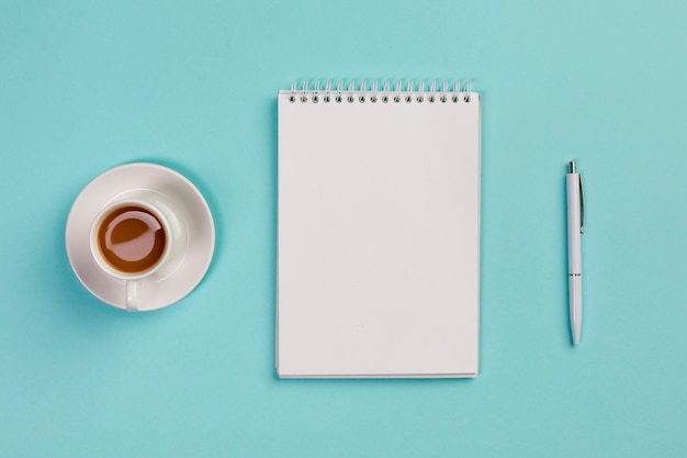 Coffee cup,blank spiral notepad and pen on blue office desk