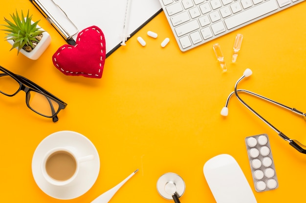 Coffee cup; blister packed medicine; keyboard; eyeglass; succulent plant; thermometer; injection; stitched heart shape; stethoscope; clipboard over yellow backdrop